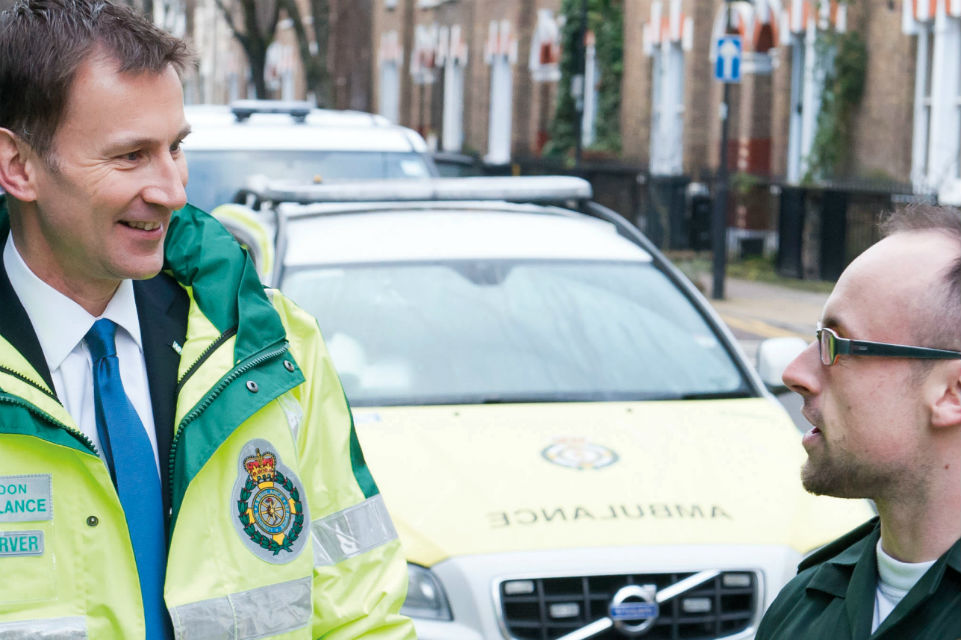 Photograph of Jeremy Hunt talking to a paramedic.