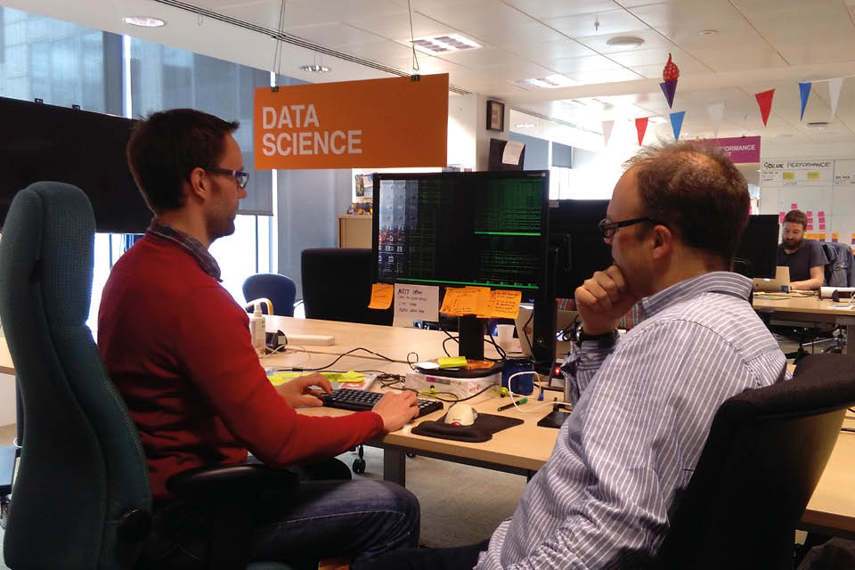 Two men at desk looking at computer screen