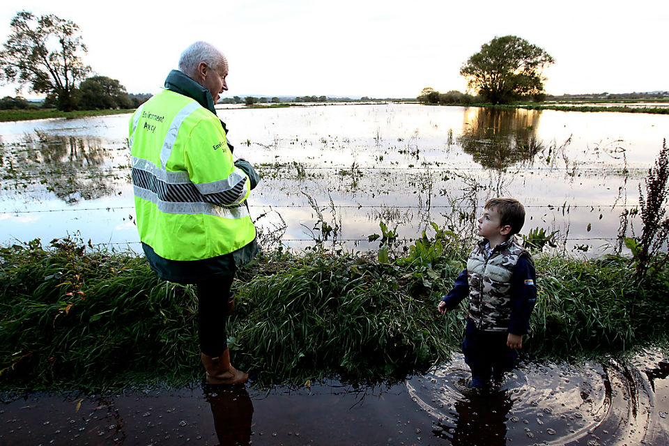 Man in high-vis jacket on flooded path with small boy