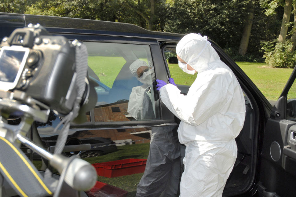 Forensic analyst working on car