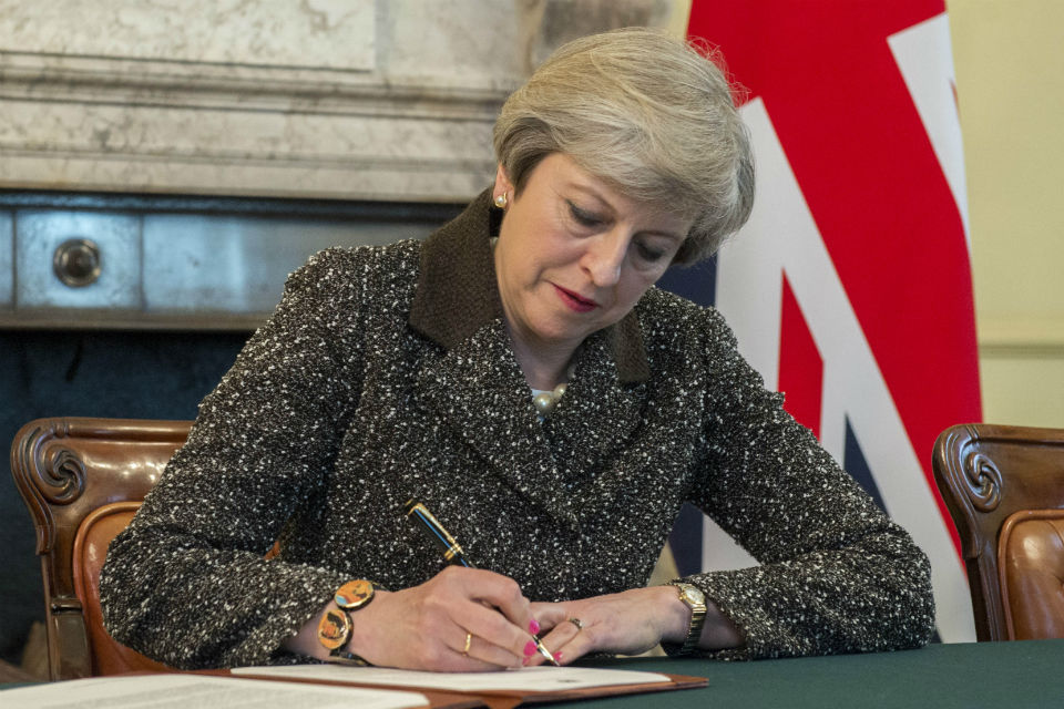 Prime Minister Theresa May signing letter