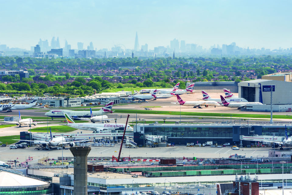 Birds-eye view of London Heathrow Airport, with London skyline in the distance