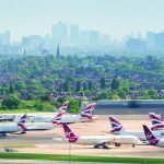 View of planes at Heathrow airport, with London skyline in the background