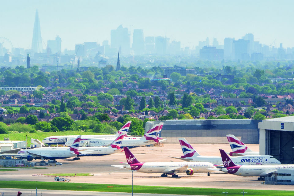 Birds-eye view of British Airways planes, and one Virgin airliner, at Heathrow airport, with London skyline in the background