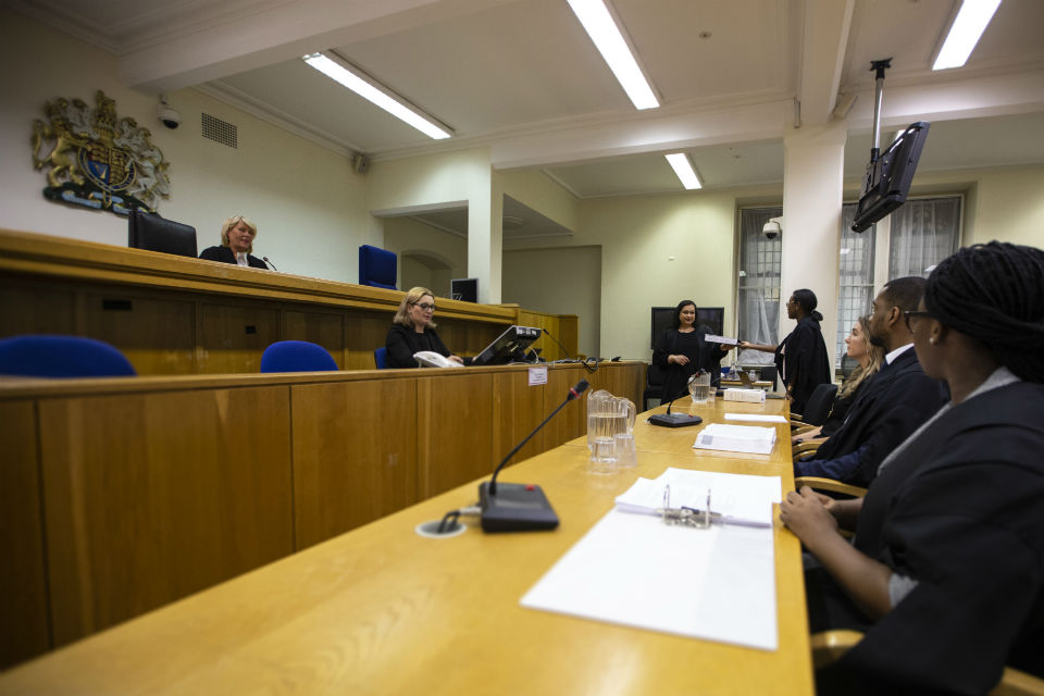 Courtroom proceedings in progress with video screens and computers in use by court officials