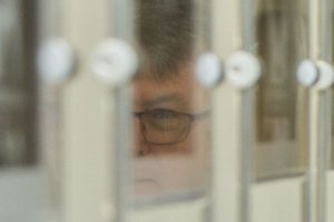 Partial reflection of Martin Parkinson in glass picture frames