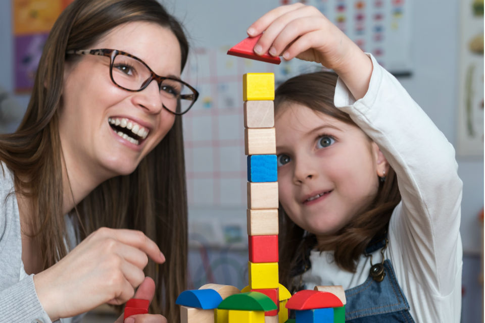 Female early years carer watching young girl build tower with toy bricks
