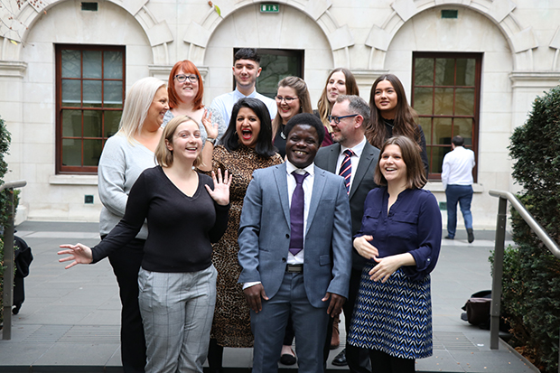 Photograph of the lead organiser of Civil Service Live in a ministry courtyard, surrounded by apprentices from various government departments who volunteered to work at Civil Service Live events in 2019