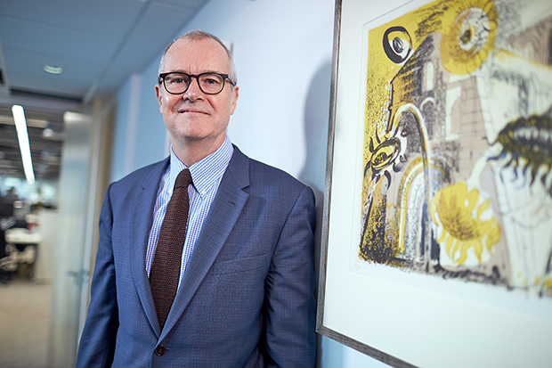 Photograph of Dr Patrick Vallance, Government Chief Scientific Adviser, in a blue suit standing by a wall next to a framed print of an abstract painting with sunflowers