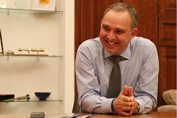 Image of Cabinet Secretary Mark Sedwill smiling and leaning forward on a table in his office
