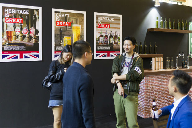 Chinese visitors at an event in Shanghai to promote UK food exports, with posters for the Britain is Great campaign in the background