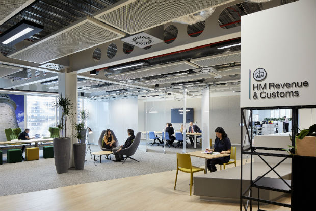 Interior view of HM Revenue and Customs offices in the Government Hub in Canary Wharf, London, showing people working at desks and in meetings