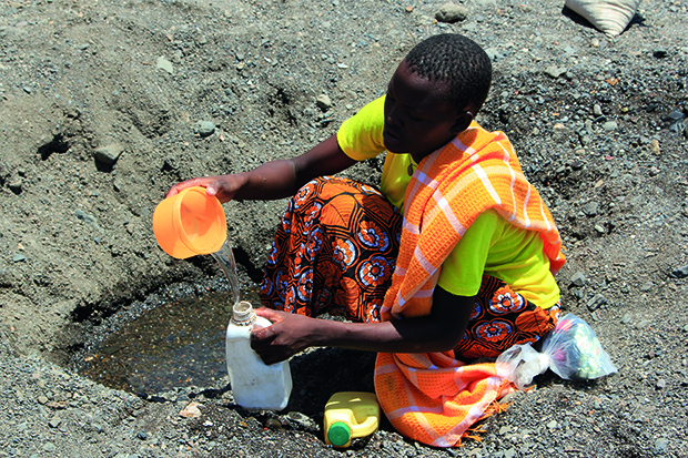 A woman scoops water from a nearly dry riverbed in northern Kenya
