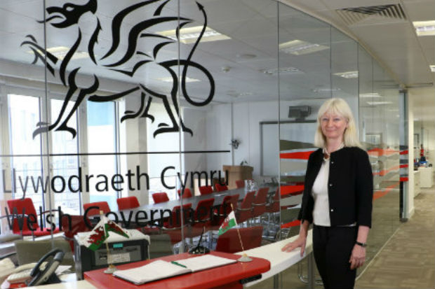 Shan Morgan, Permanent Secretary of the Welsh Government, standing by a glass fronted office with the Welsh dragon imprinted on in it.