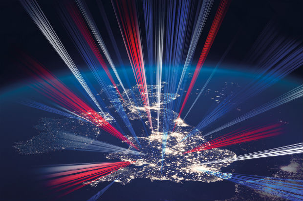 Image from space of the United Kingdom at night, showing light from major conurbations and with shafts of light in red, white and blue emanating from the land mass