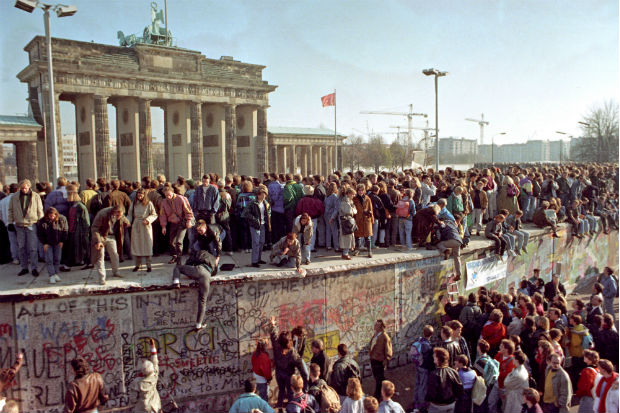Berliners stand on a section of the Berlin Wall, two days after the fall of the GDR on 11 November 1989