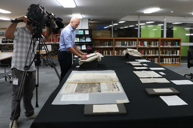 Staff at The National Archives photographing historical documents laid out on a table